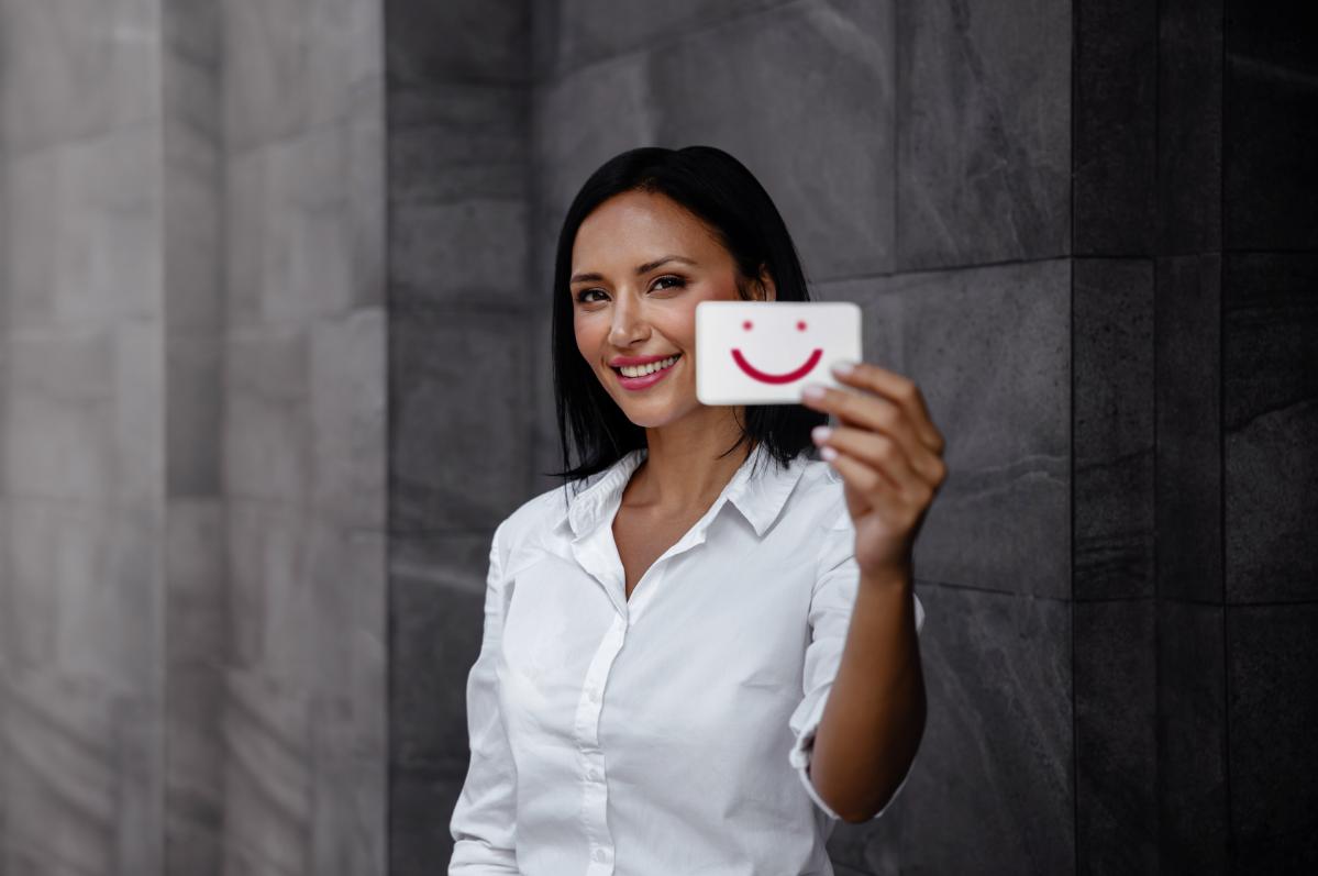 Lächelnde Frau, die eine Smilie Karte hält