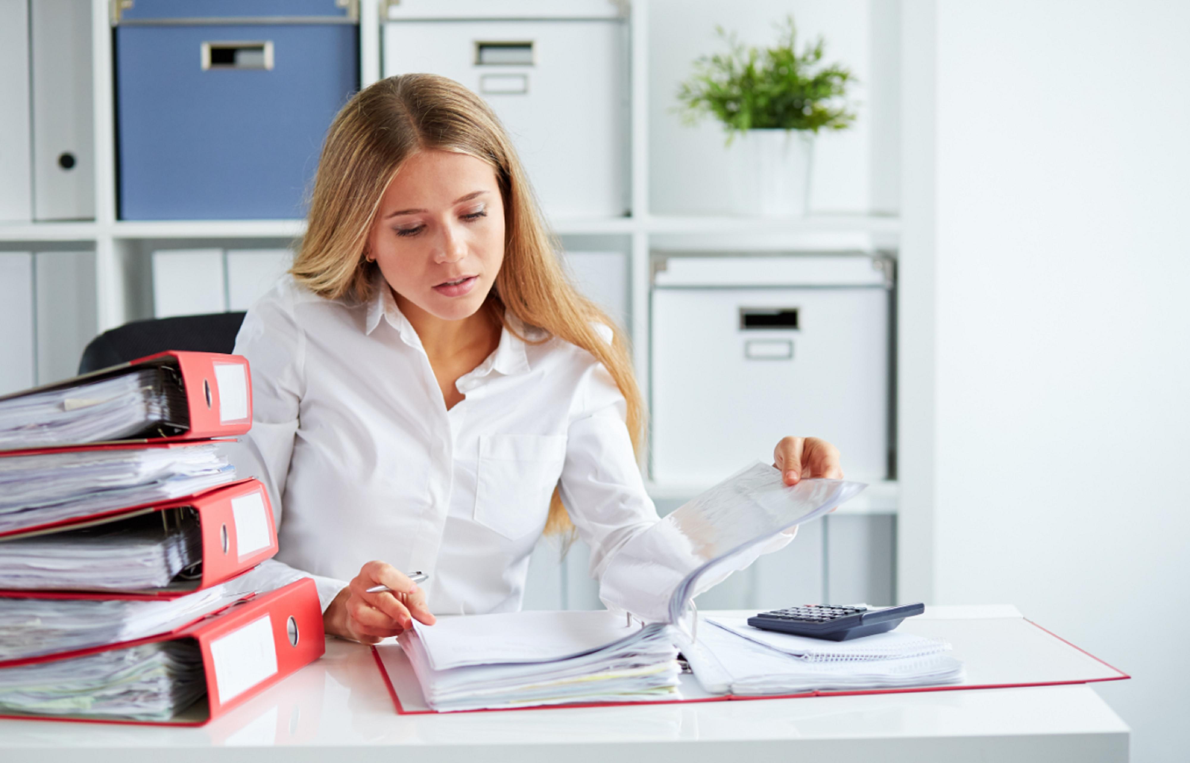 Frau mit Dokumenten am Schreibtisch sitzend
